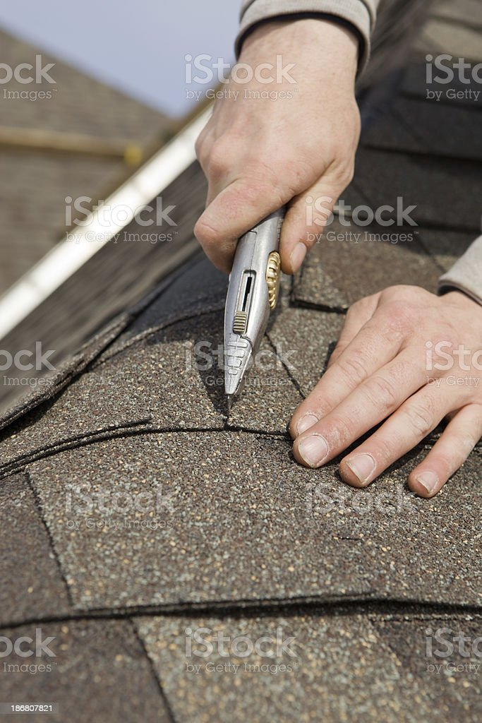 Roofer Trimming a New Shingle on Home Construction Project stock photo