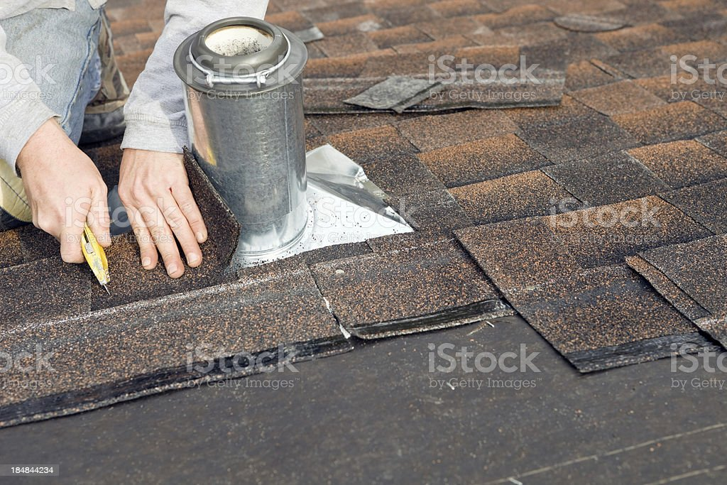 Roofer Trimming Shingle around Plumbing Vent Flashing stock photo