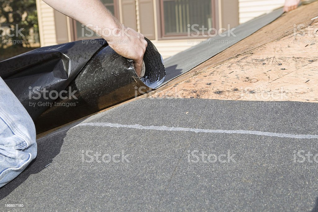 Roofer Unrolling Weather Guard Tar Paper stock photo