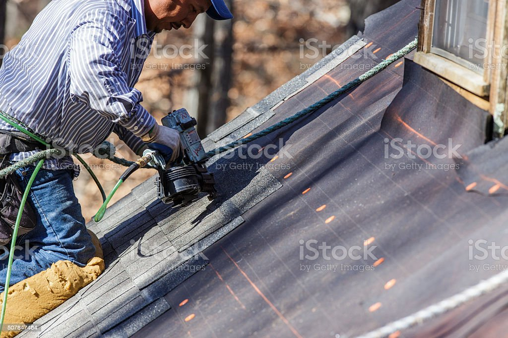Roofer uses nail gun to secure shingles. stock photo