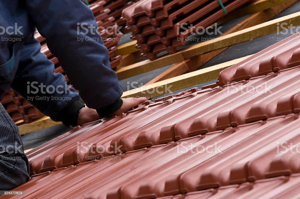 Roofer when placing of roofing tiles stock photo