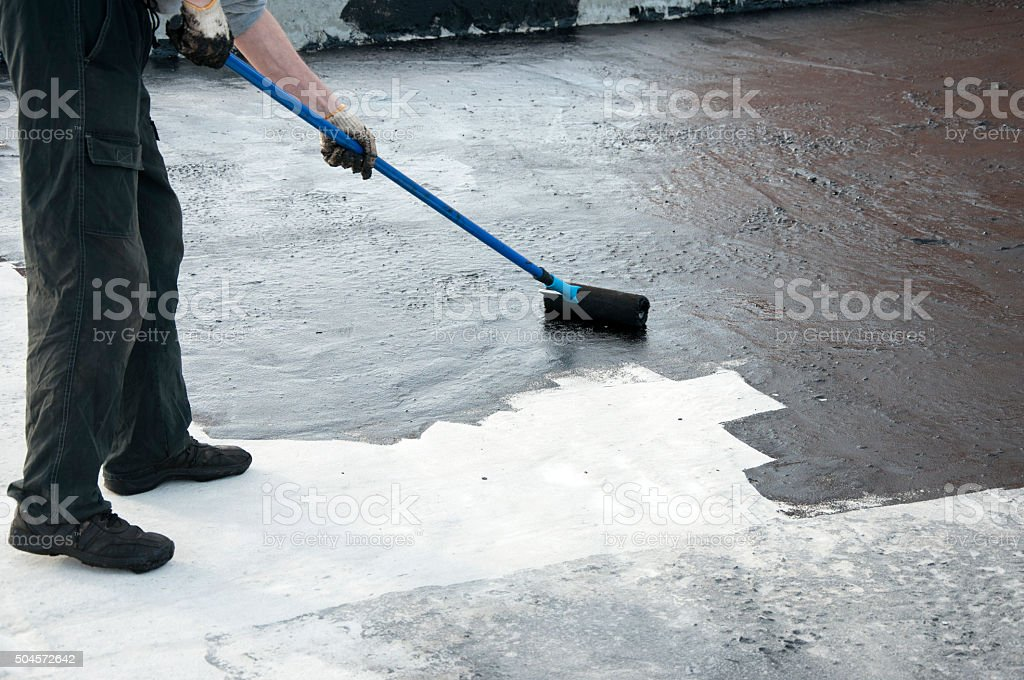 Roofer worker painting   roller brush,  waterproofing stock photo