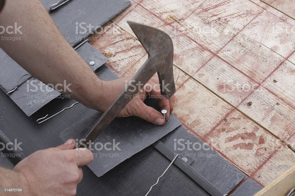 A roofer's hands using a hammer to lay roofing shingles stock photo