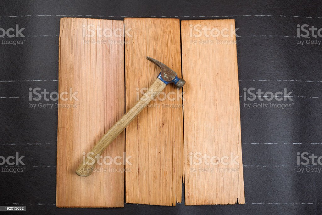 roofing hammer with new cedar wood shingles on felt paper stock photo