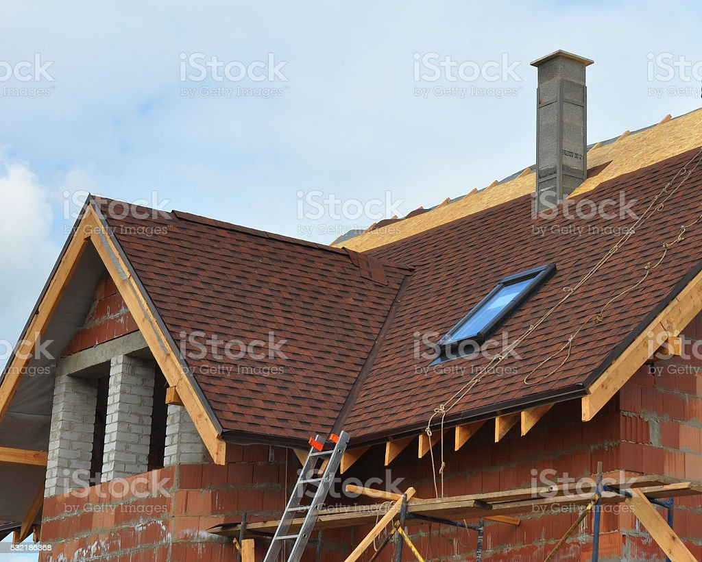 Roofing with modular chimney, bitumen tile, skylights and eaves. stock photo