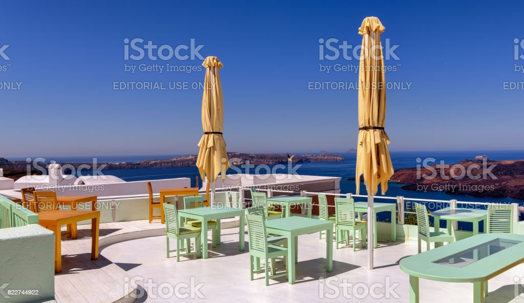 Rooftop patio bar in the island of Santorini offers views of the blue Aegean sea. stock photo