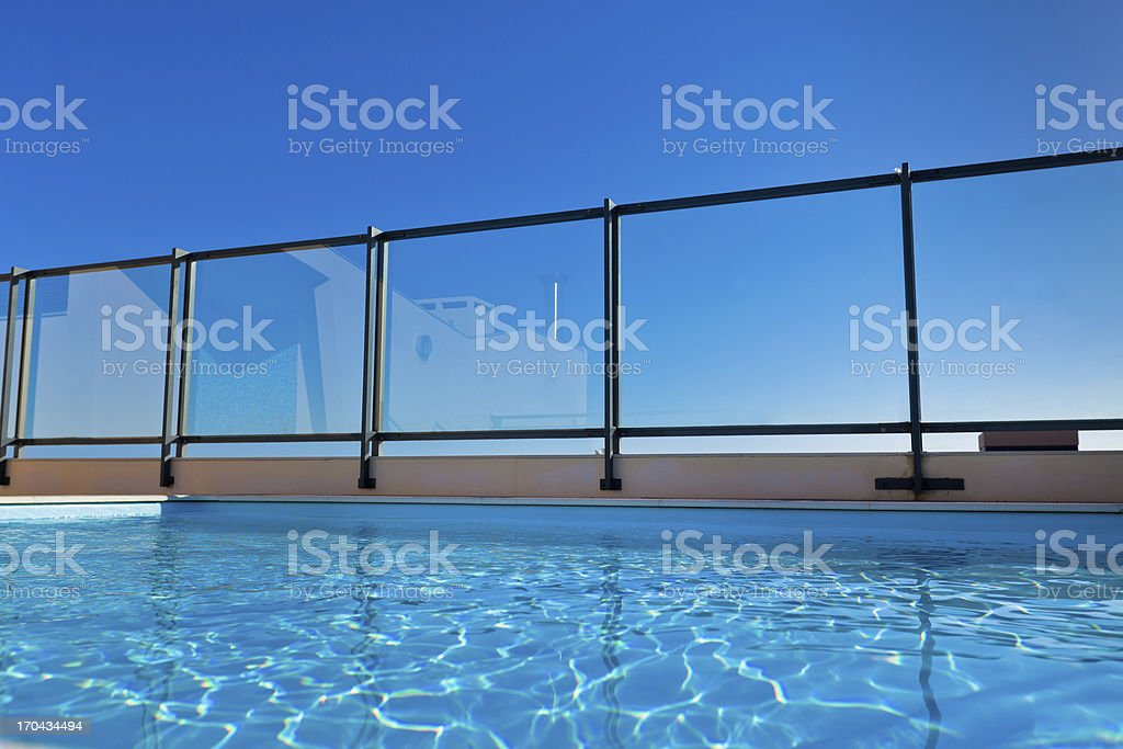 A rooftop pool with a glass rail on a sunny day royalty-free stock photo