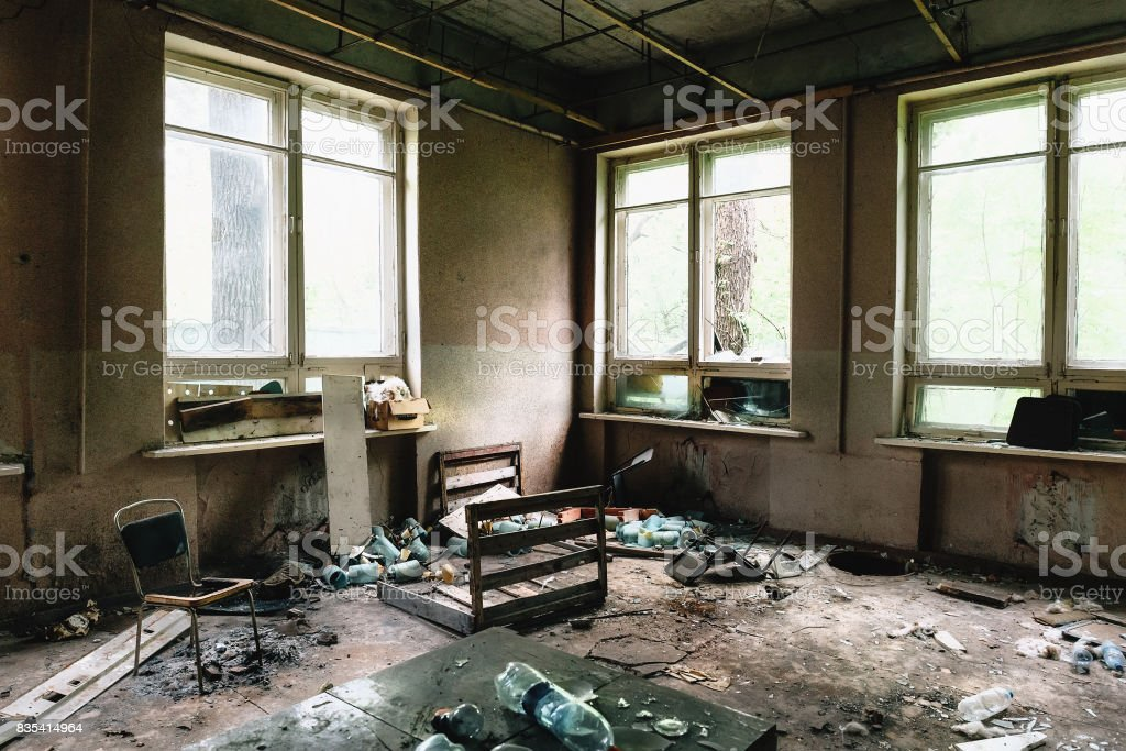 Room with big windows and furniture in old ruined abandoned building stock photo