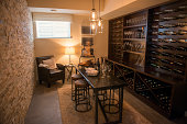 Room with dark dining furniture and wine filled shelves