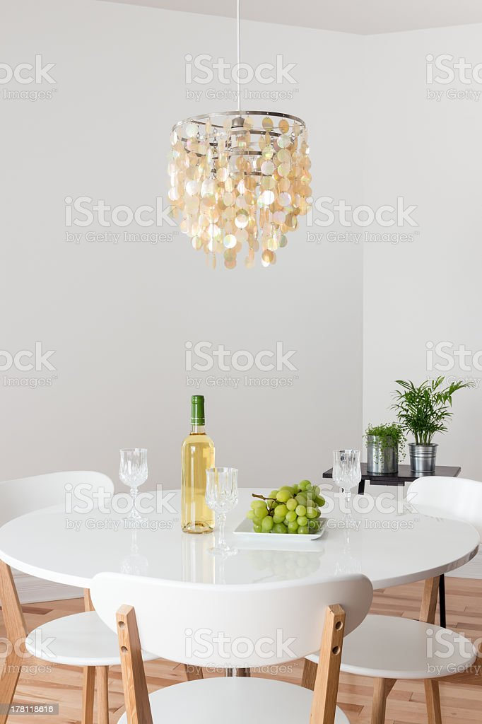 Room with decorative chandelier, white round table and plants.