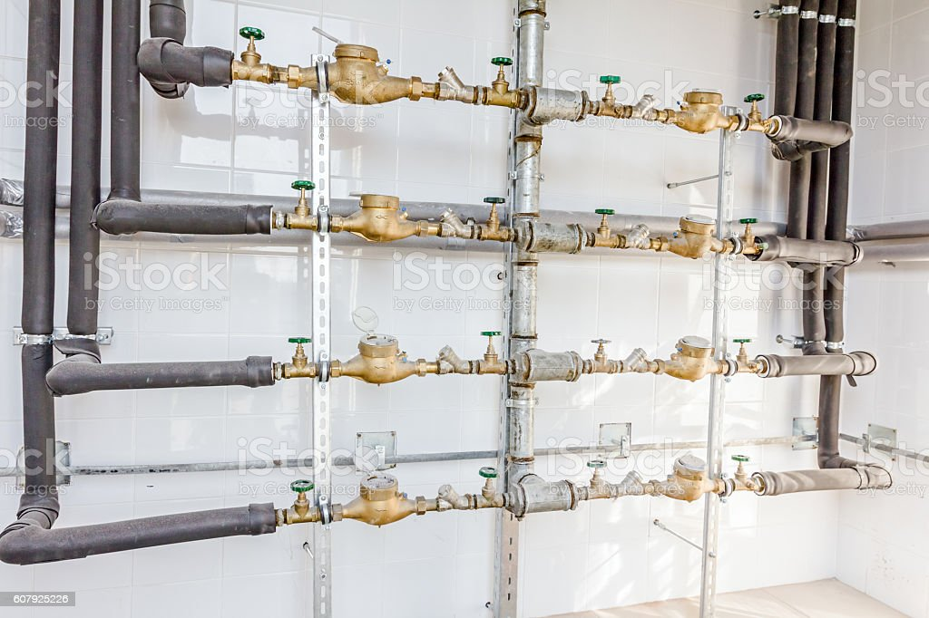 Room with lined up water meters, pipes and valves stock photo