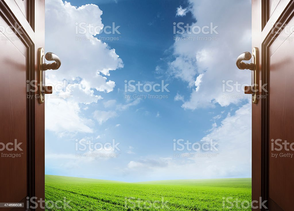 room with open door to the meadow with green grass stock photo