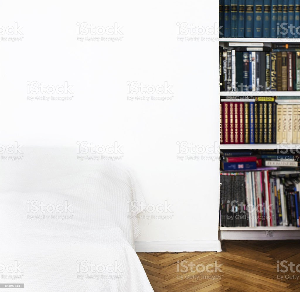 Room with White walls, bed,  book case and parquet floor. royalty-free stock photo