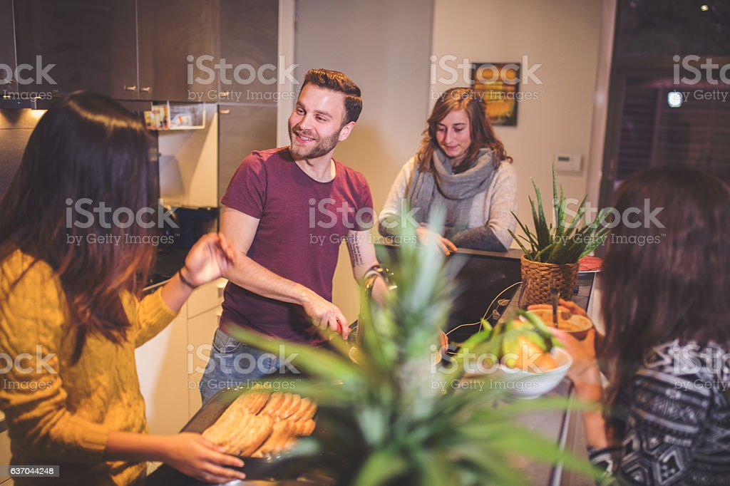 Roommates cooking together stock photo
