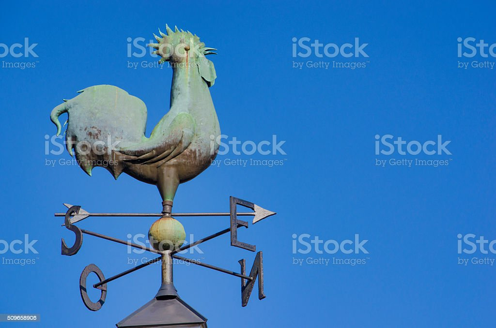 Rooster weather vane over blue sky stock photo