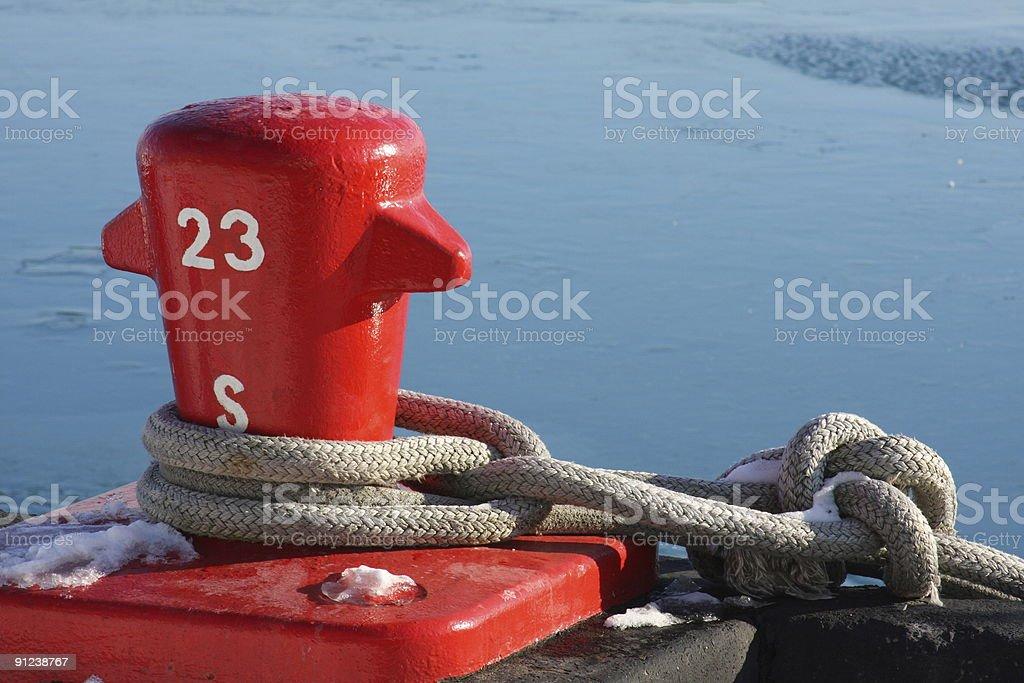 Rope around red dock bollard stock photo