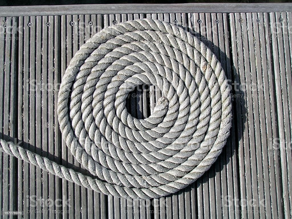 Rope coiled on dock stock photo