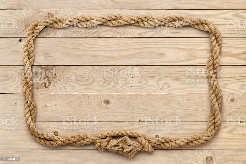 Rope frame on weathered light brown wooden board stock photo