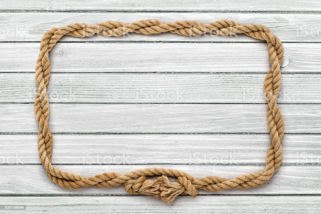 Rope frame on weathered white painted wooden board stock photo