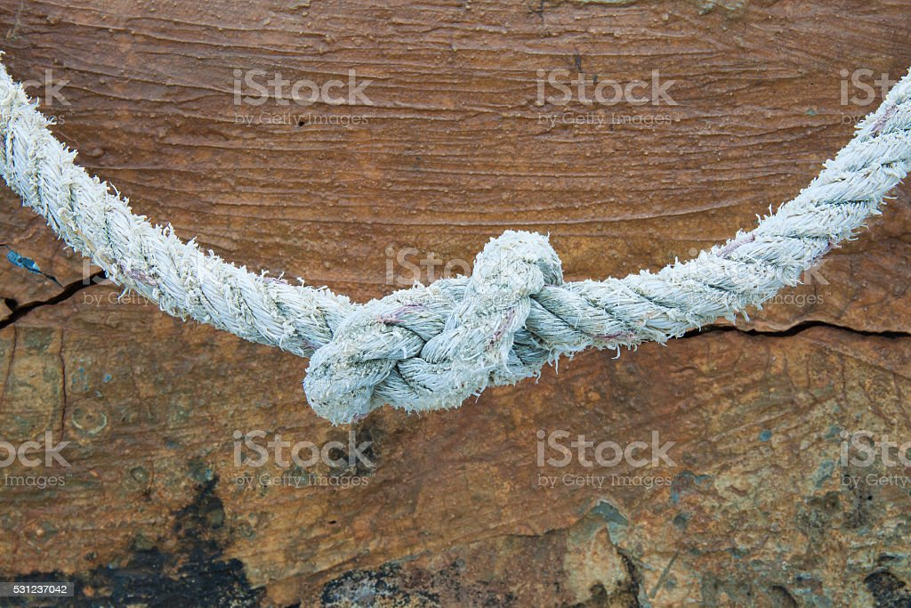Rope knot on maroon background royalty-free stock photo