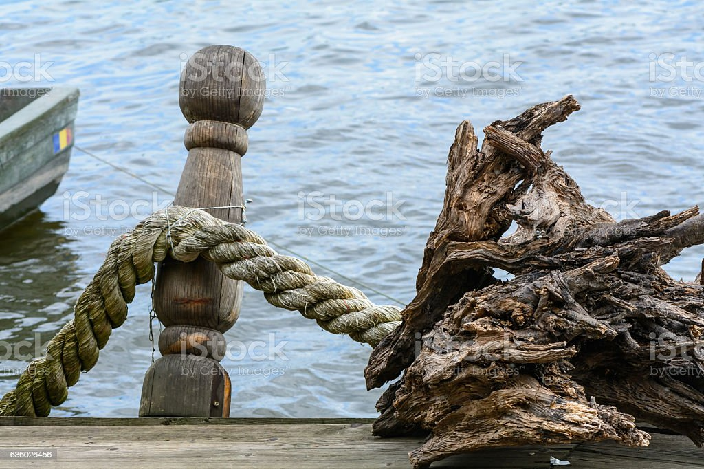 Rope knotted along a ship bollard. Docks with rope in stock photo