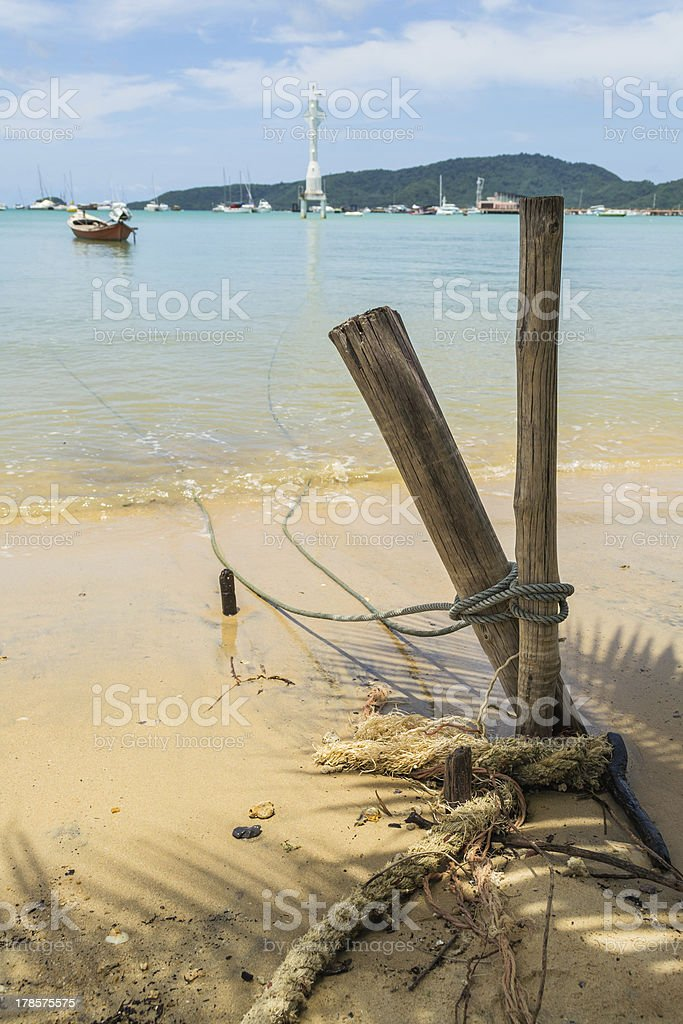 rope of a boat is tie up with wooden stake royalty-free stock photo
