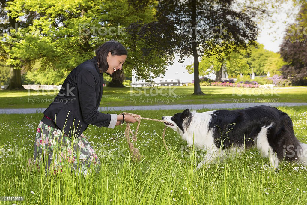 Rope pulling with her dog stock photo