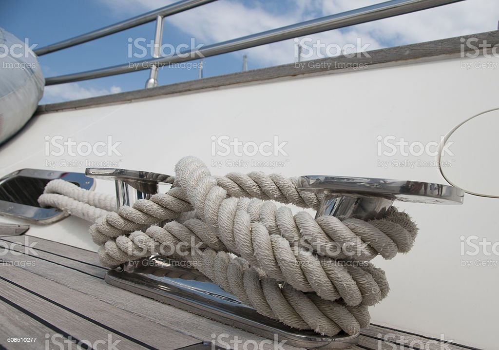 Rope rolled up around stainless steel Bitt on Yacht stock photo