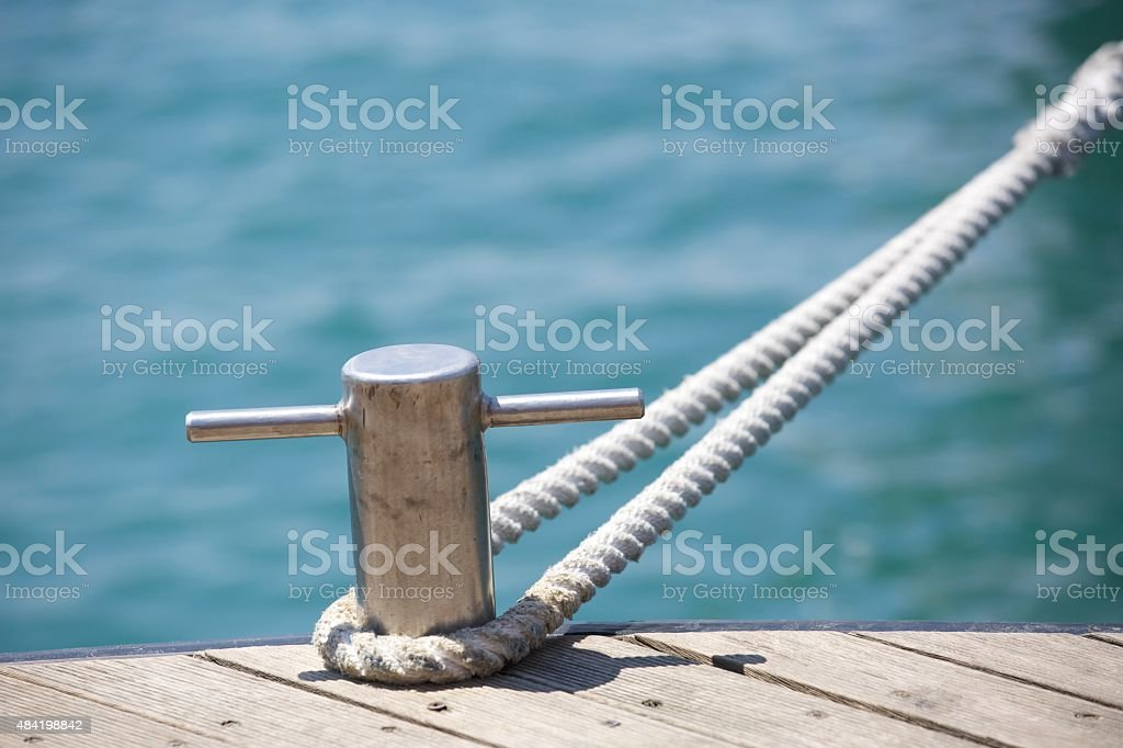 Rope secured to a harbour bollard stock photo