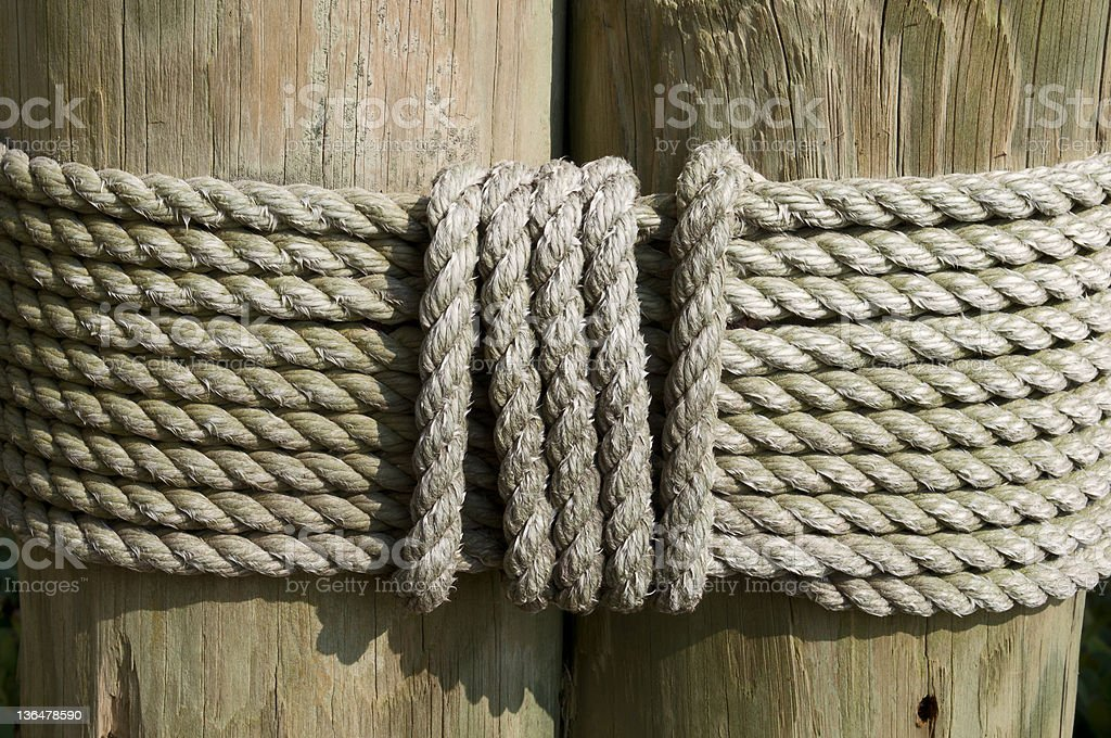 Rope tied around dock piling royalty-free stock photo
