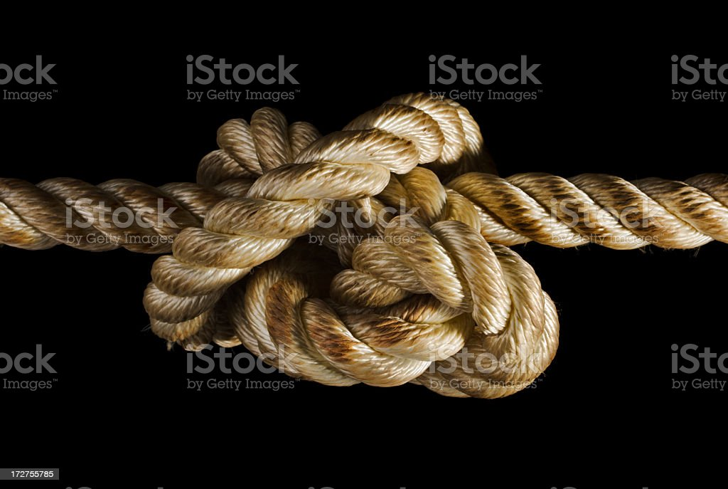Rope Tied Knot Expressing Stress, Adversity, Tension, Pulling on Black royalty-free stock photo