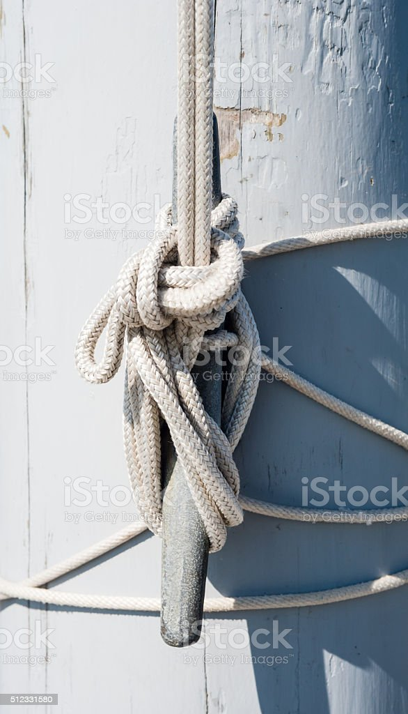 Rope tied on cleat casting shadow on white mast stock photo
