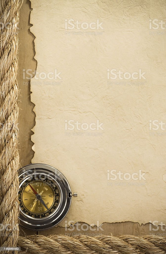 ropes and compass at old paper background royalty-free stock photo