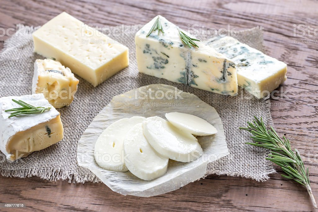 Roquefort, briee, and other cheese over a fabric stock photo