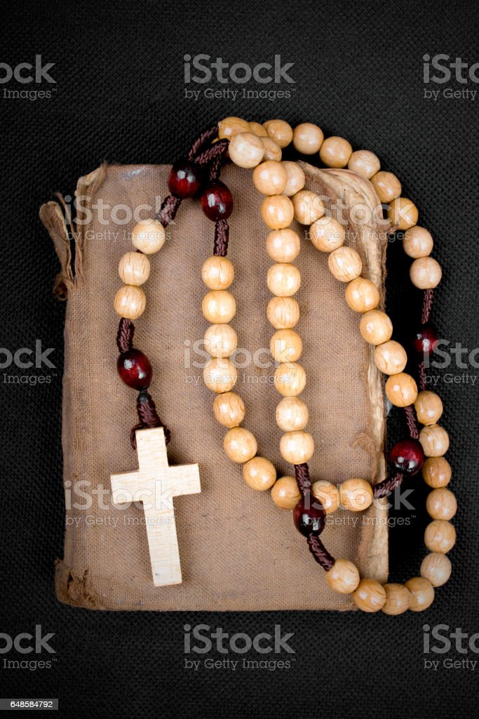 rosary and prayer book on a dark background stock photo
