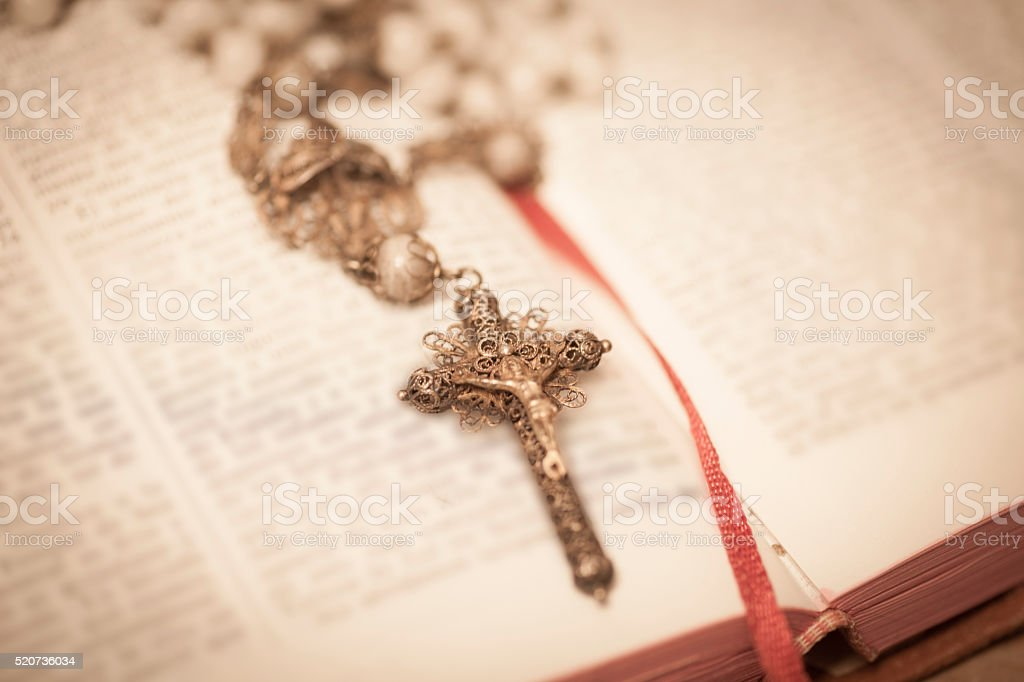 Rosary on open Bible stock photo