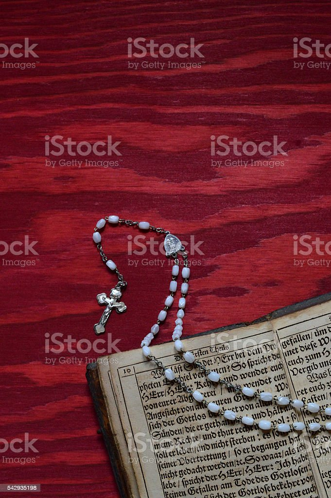 rosary with ancient book on red table stock photo
