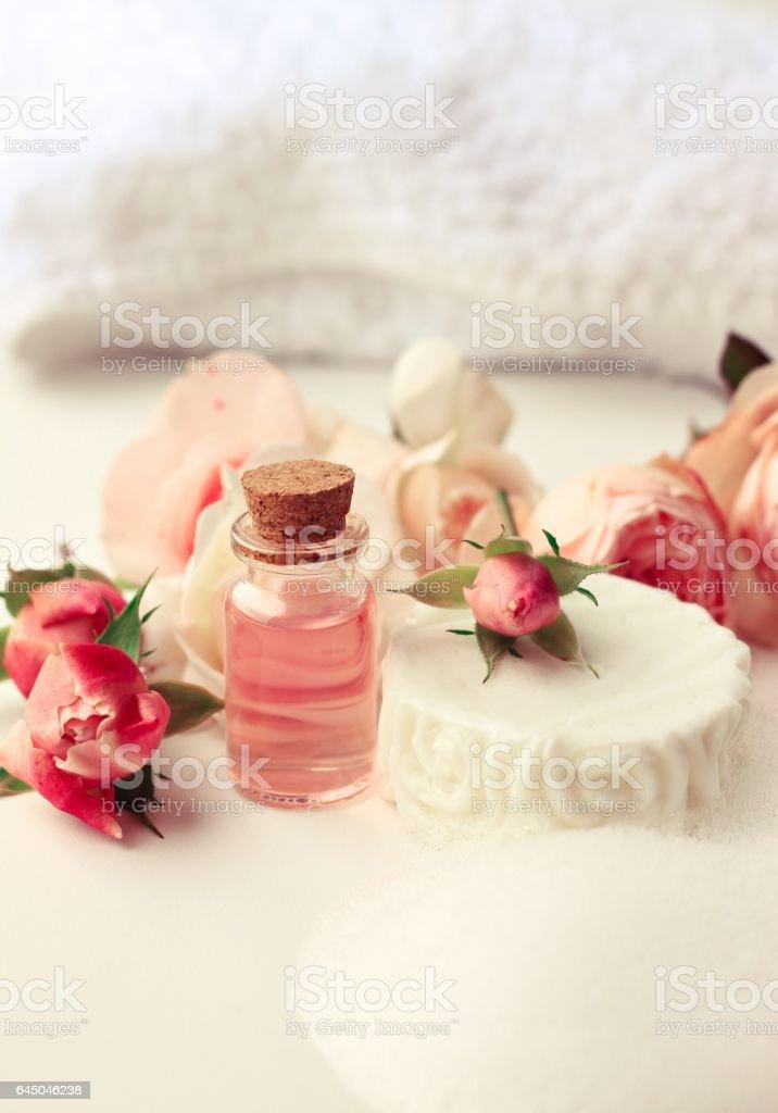 Rose aroma attar, white soap bar with foam, fresh pink garden flowers. stock photo