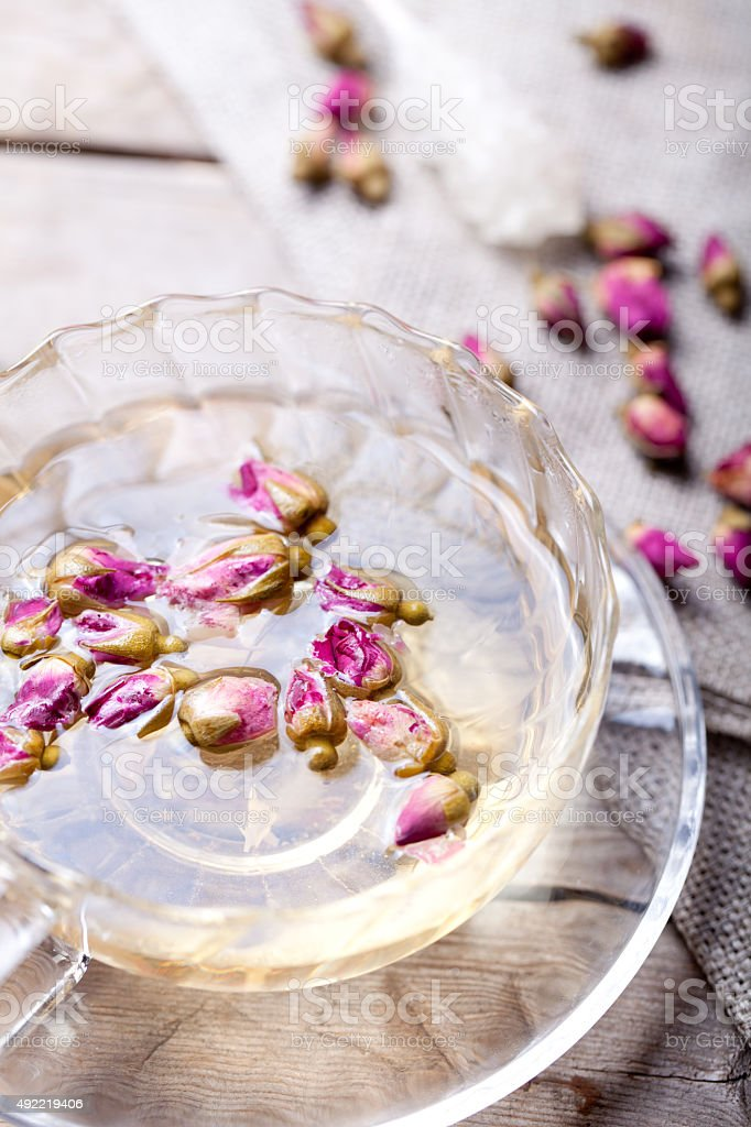 Rose buds herbal tea in a glass cup stock photo