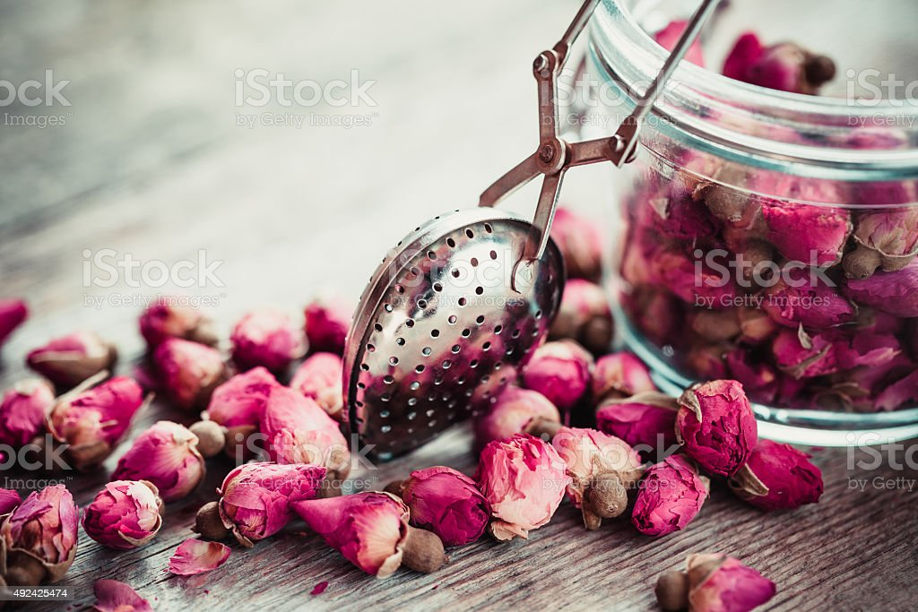 Rose buds tea, tea infuser and glass jar. stock photo
