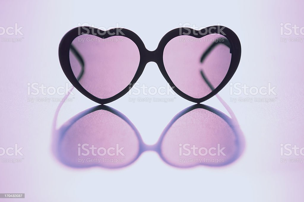 Rose Colored Glasses Sit on Reflective Background stock photo