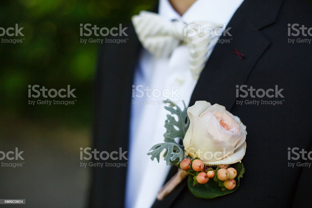 rose on suit jacket of groom stock photo