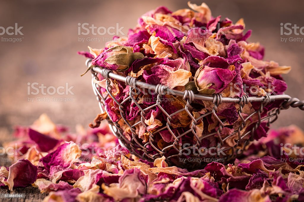 rose petals and dried flowers in spoon on old wooden table