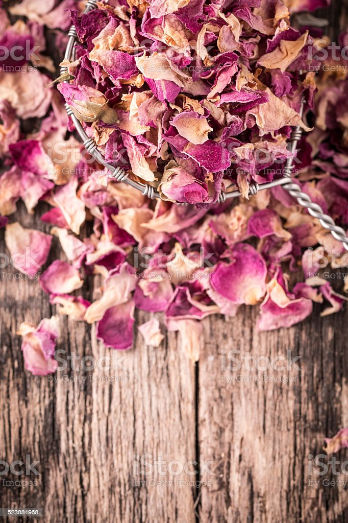 rose petals and dried flowers in spoon on  wooden table stock photo