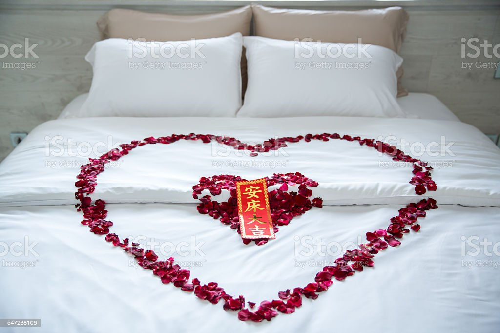 Rose Petals at romantic wedding bed stock photo