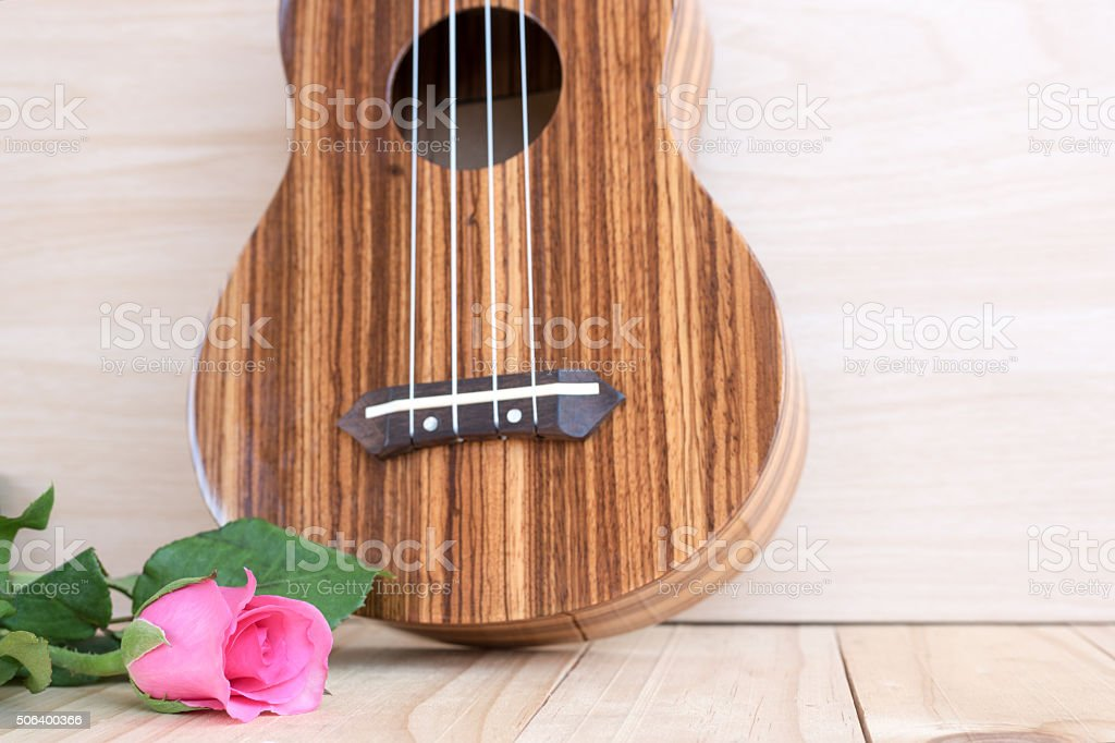 rose with ukulele on wooden background stock photo