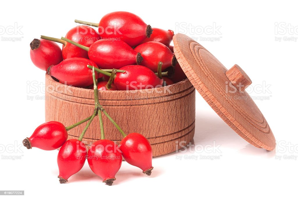 rosehip berries in a wooden bowl isolated on white background stock photo