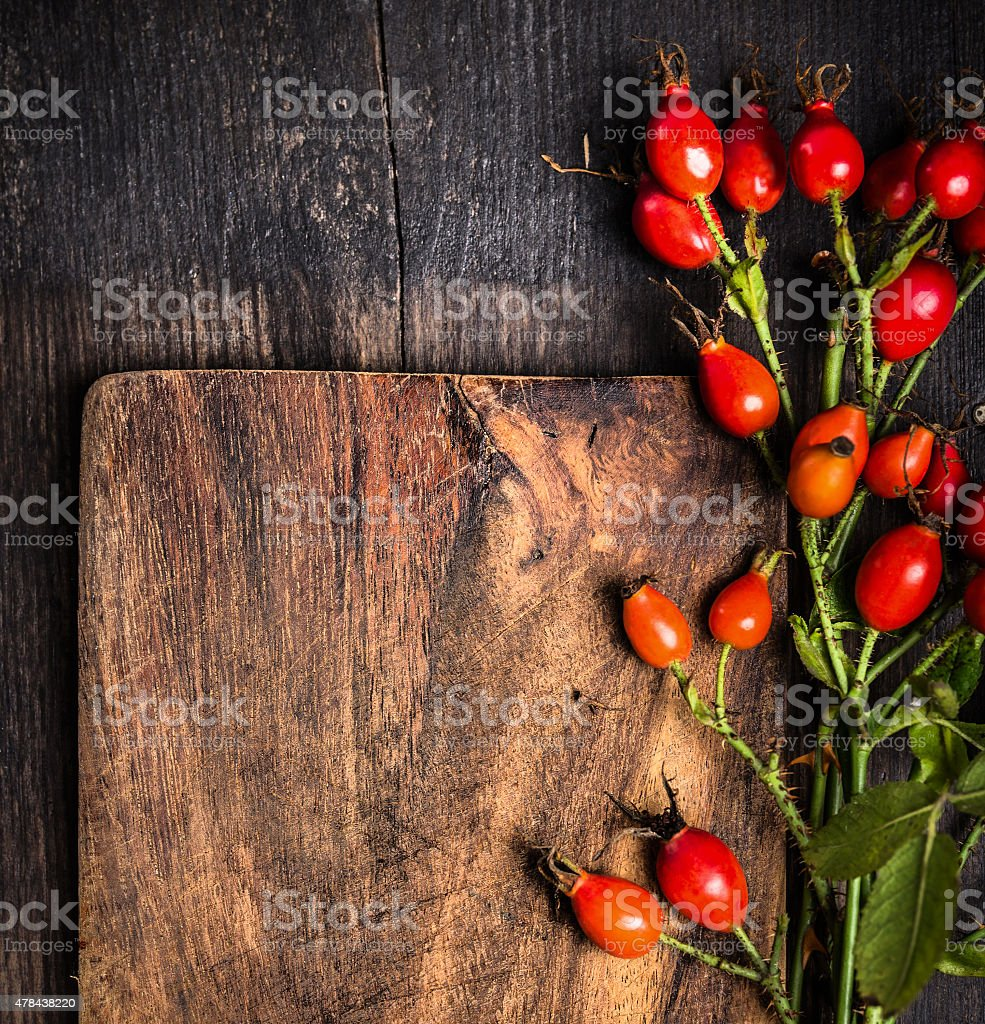 Rosehips on old wooden board, top view, autumn background stock photo
