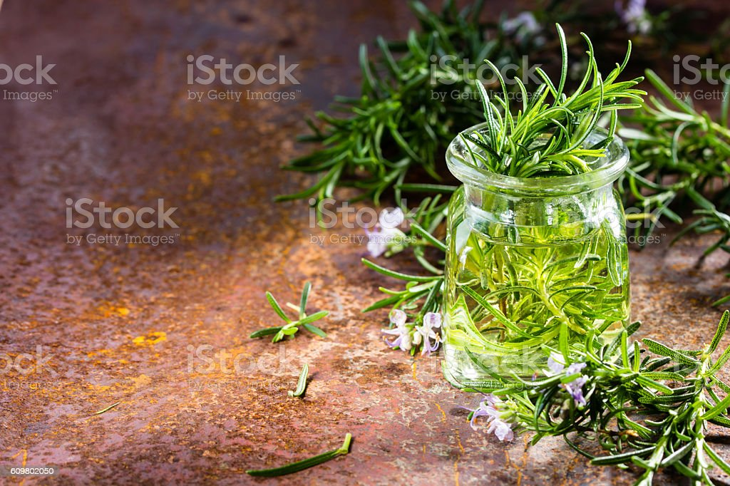 Rosemary essential oil jar and plant with flowers, rustic background stock photo