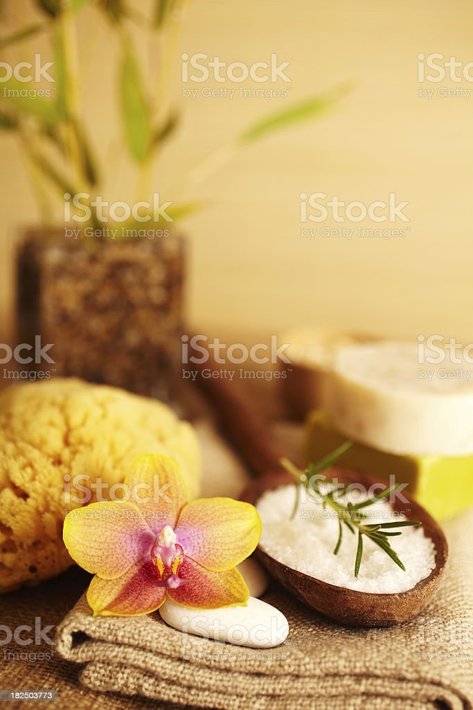 Rosemary on bath salt scrub in wooden spoon and flower royalty-free stock photo